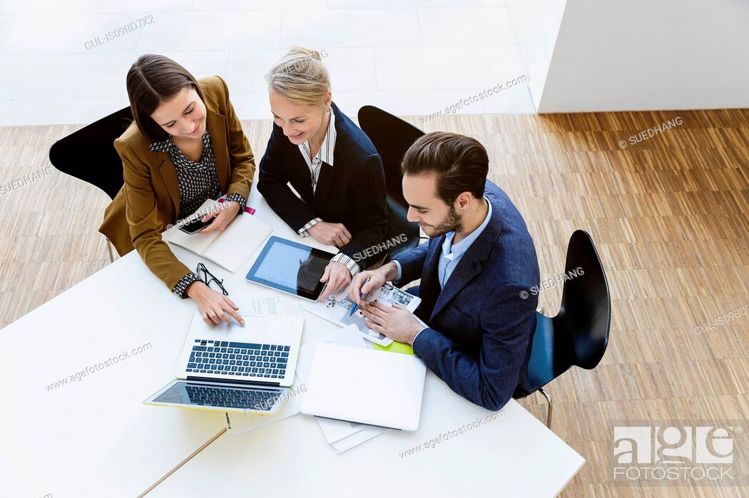 Stock Photo: Colleagues in meeting using digital tablet and laptop.
