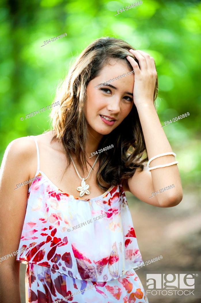 Stock Photo: Portrait of a smiling 14 year old brunette girl in a summer dress in an outdoor setting.