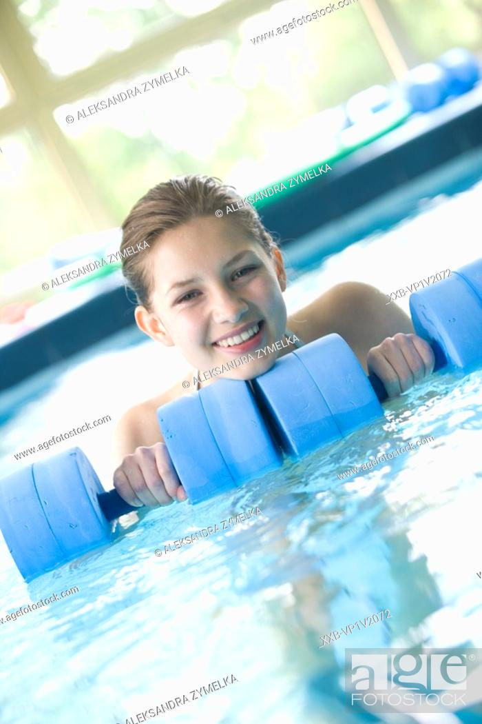 Stock Photo: young woman doing exercise in swimming pool.