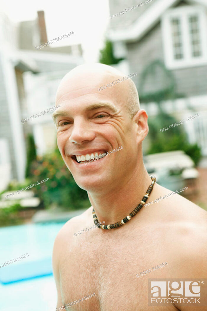 Stock Photo: Young man smiling by pool.