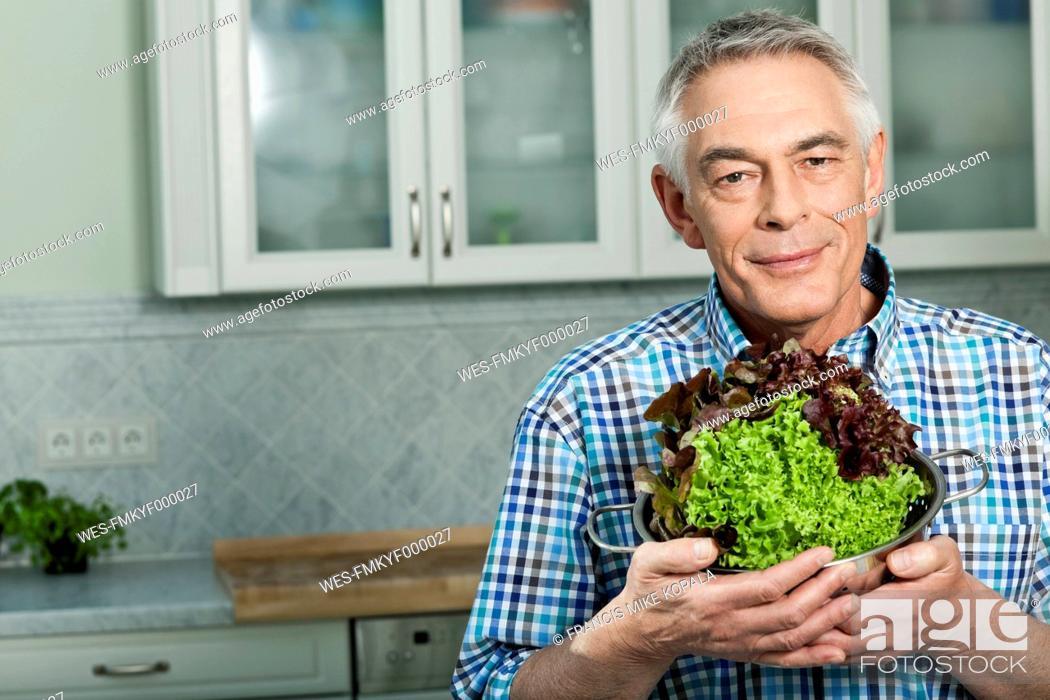 Stock Photo: Germany, Berlin, Senior man holding vegetables, portrait.