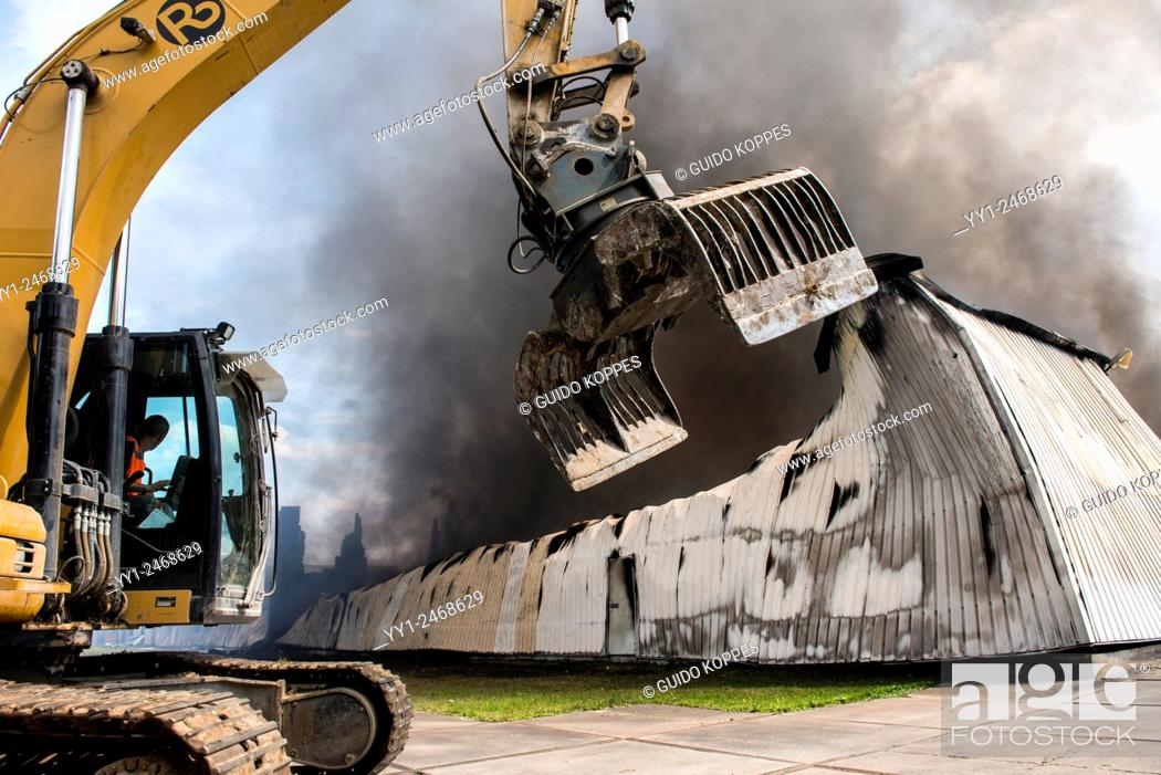 Stock Photo: Tilburg, Netherlands. A large fire blazing inside a warehouse for plastic garden furniture at an industrial estate, with smoke nuisance as a result.