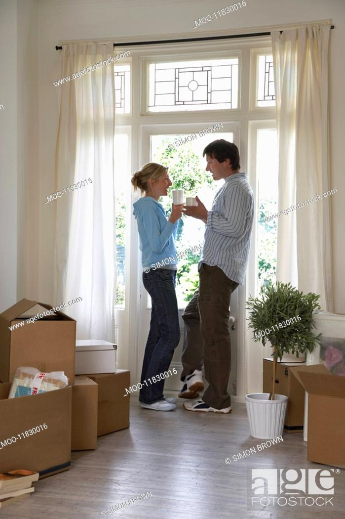 Stock Photo: Couple standing by window surrounded by boxes.