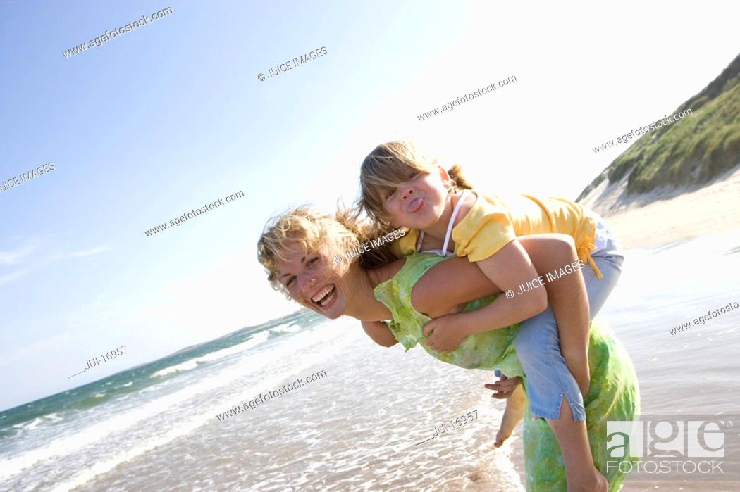 Stock Photo: Portrait of mother piggybacking daughter on beach.