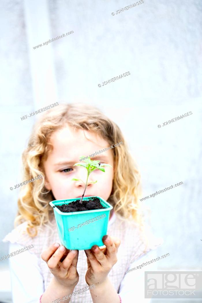 Stock Photo: Girl holding seedling in pot.