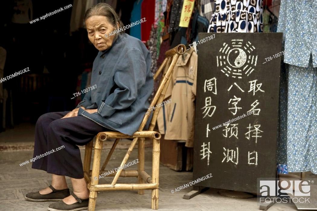 Stock Photo: Woman sitting at the door of his house. Langzhou, China.