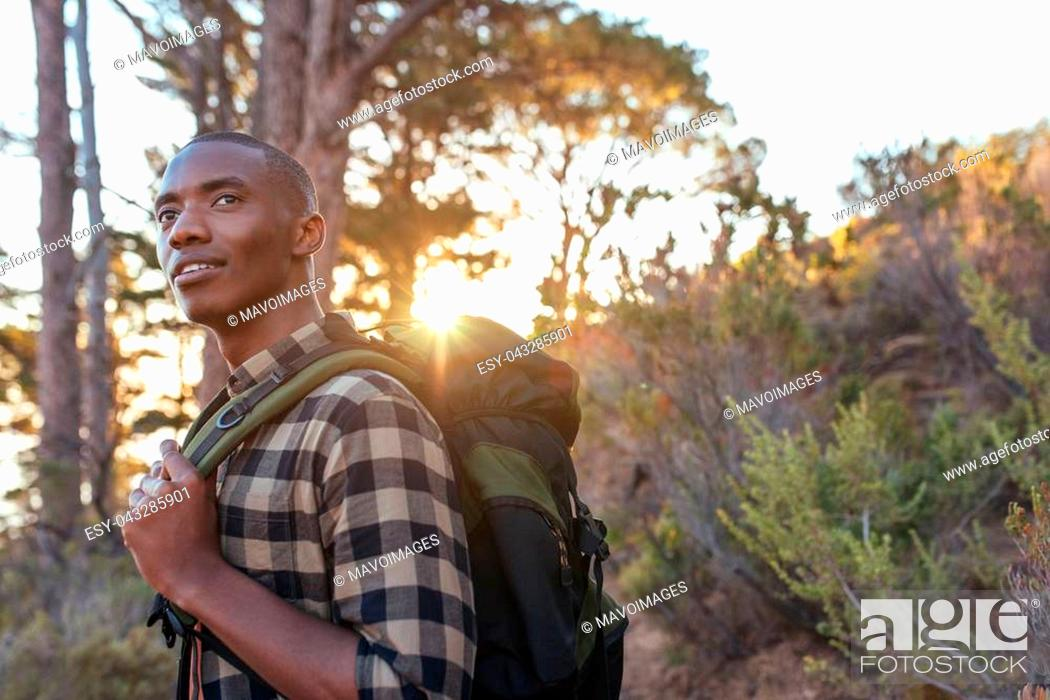 Stock Photo: Young African man wearing a backpack standing on a trail looking at the view while hiking alone in the late afternoon.