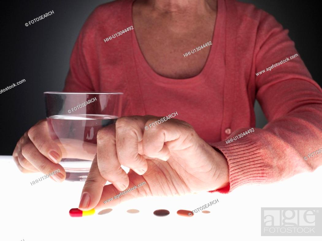 Stock Photo: Woman taking pill (close-up).