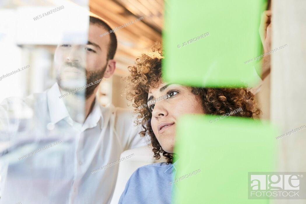 Stock Photo: Two colleagues brainstorming with post-its on glass pane.