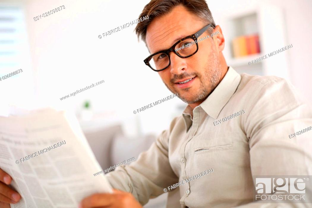 Stock Photo: Friendly guy with eyeglasses reading newspaper.