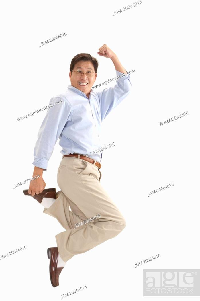 Stock Photo: Husband, Man jumping in mid-air with arms raised and smiling.