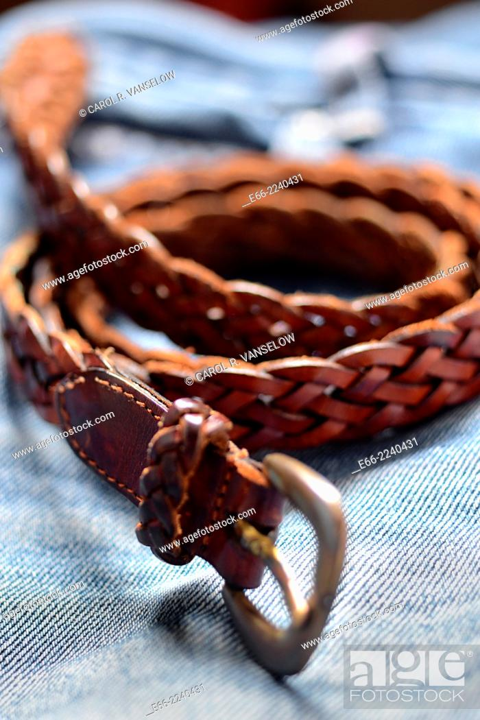 Stock Photo: belt of woven Morrocan leather curled up, lying on blue jeans. Shot with LensBaby for selective focus.