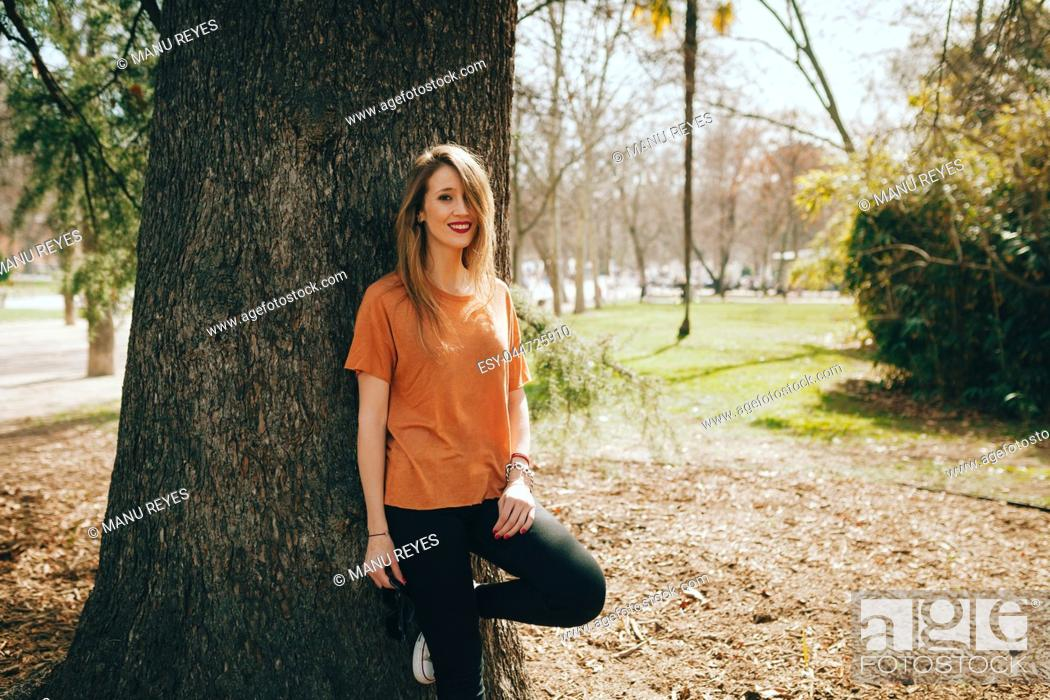 Stock Photo: Young smiling blonde woman supported on a tree with black jeans.