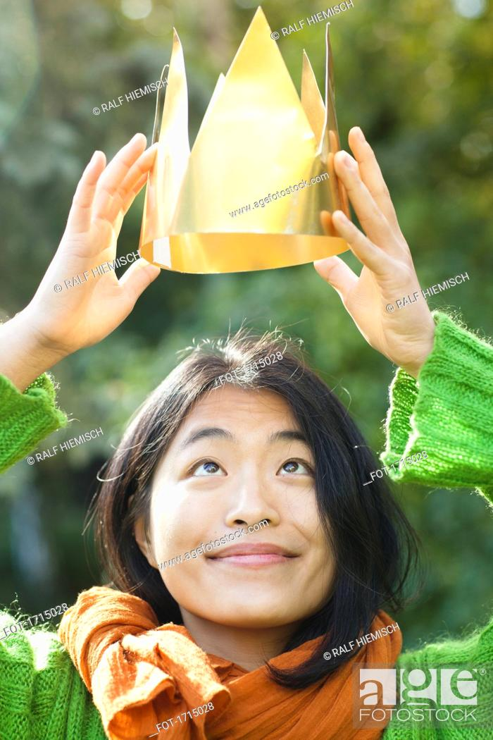 Stock Photo: Close-up of woman looking up while holding crown during sunny day.