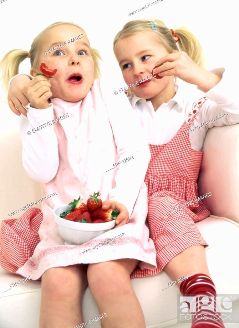 Stock Photo: Two girls enjoying strawberries.