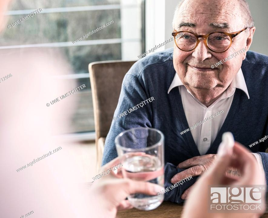 Stock Photo: Woman holding pill and glass of water for smiling senior man.