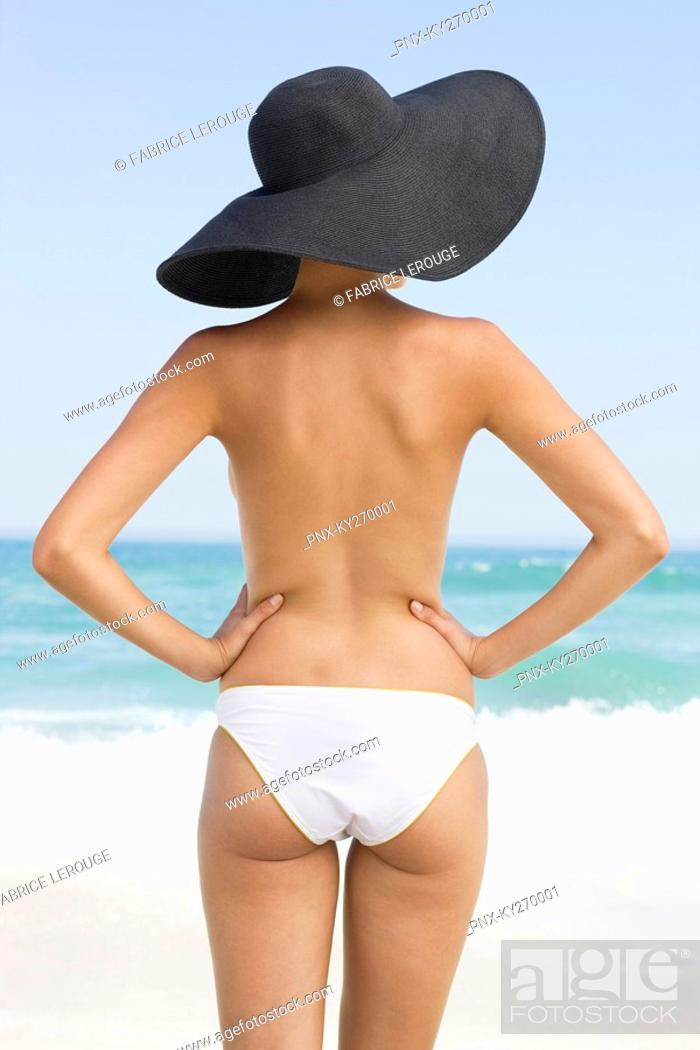 Stock Photo: Rear view of a woman standing on the beach with her arms akimbo.