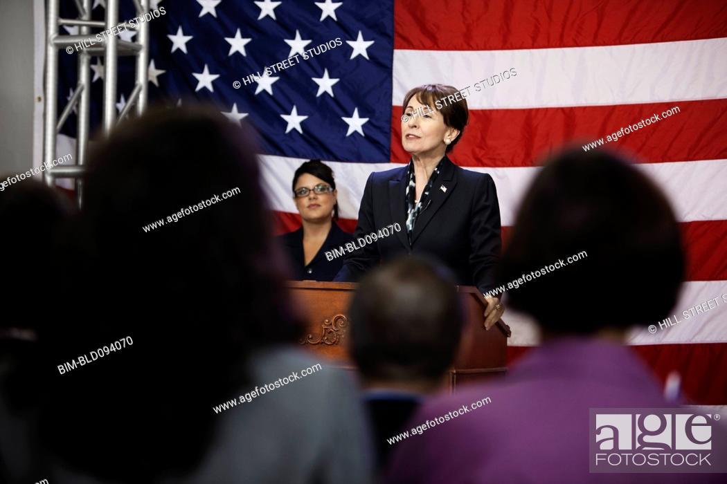 Stock Photo: Female politician making speech at podium.