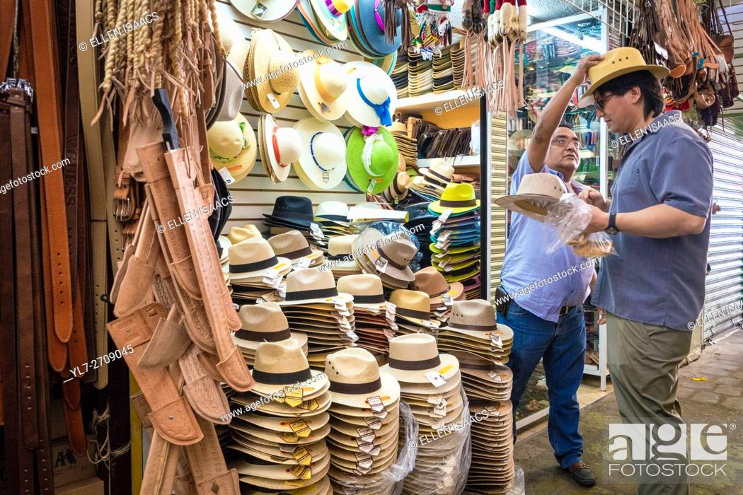 Stock Photo: Salesman reacing to put a straw hat on a customer at a market in Oaxaca Mexico.