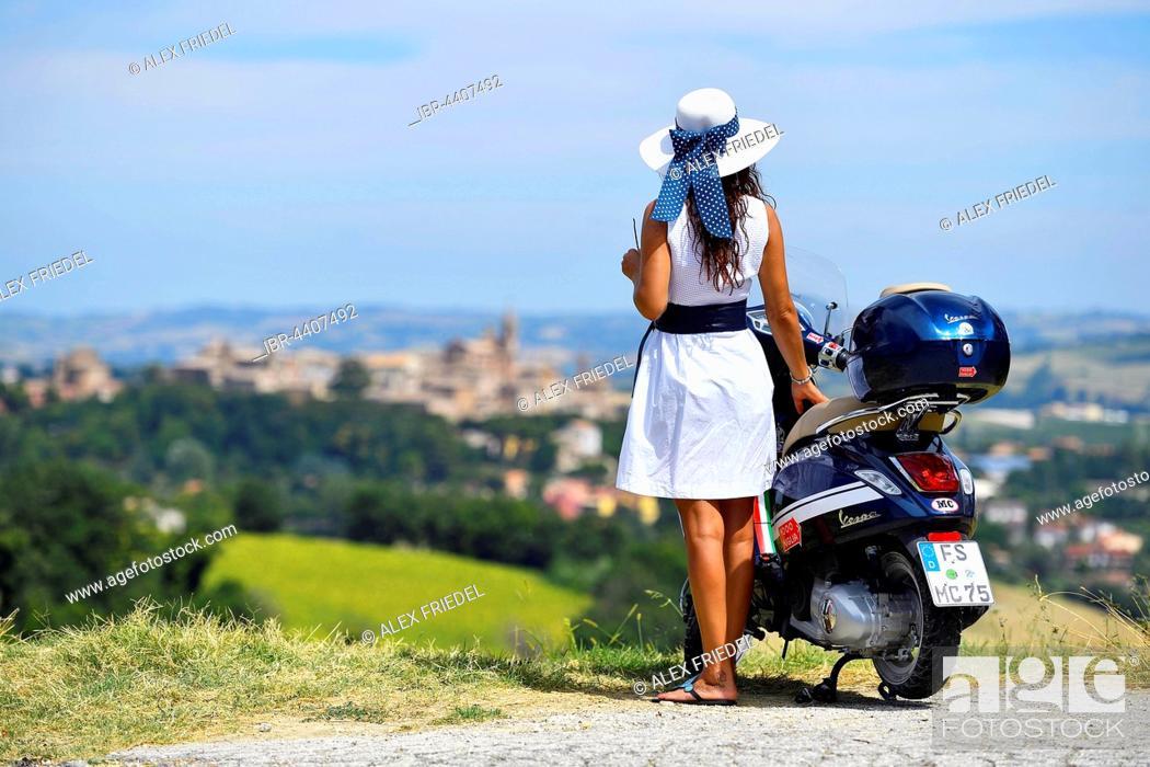 Stock Photo: Woman with white sunhat next to Vespa Primavera scooter, Corinaldo, Marche, Italy.