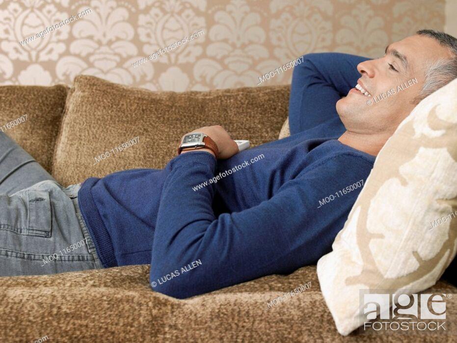 Stock Photo: Smiling man laying on sofa.