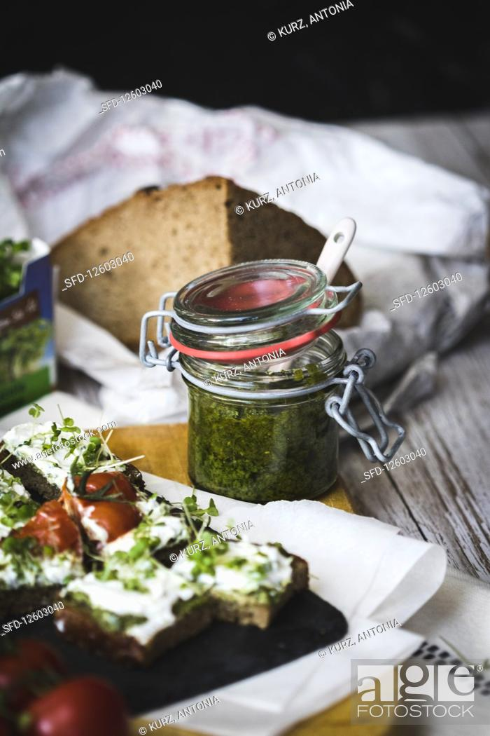 Stock Photo: Pesto in a flip-top jar with a slice of bread topped with cream cheese and cress.