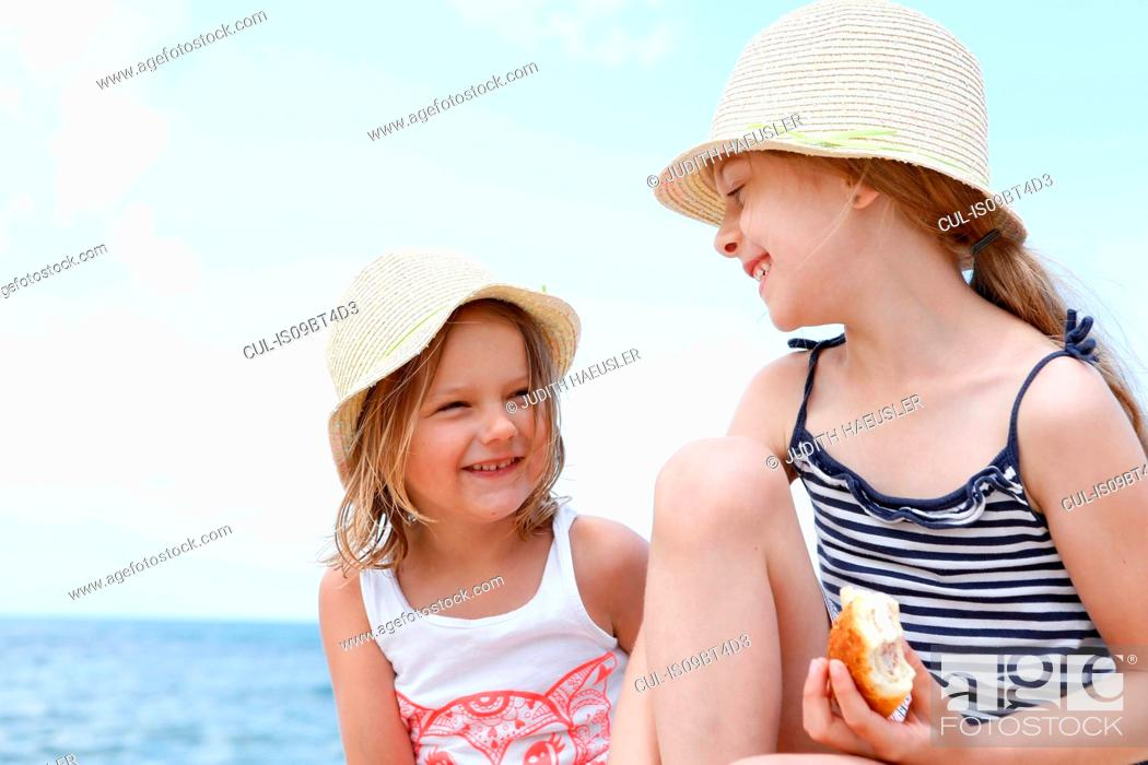 Stock Photo: Two girls in sun hats eating sandwiches on beach, Scopello, Sicily, Italy.