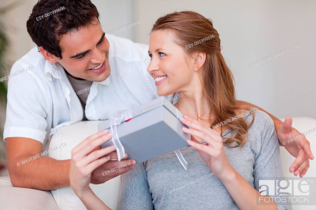 Stock Photo: Young woman smiling happily about the present she just got from her boyfriend.
