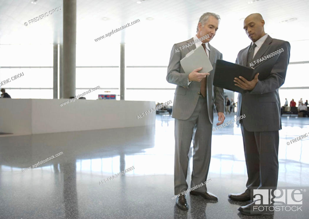 Stock Photo: Two businessmen standing and talking in airport concourse.