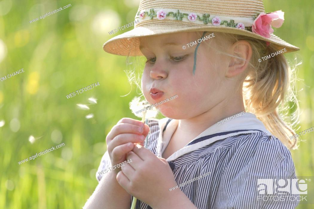 Stock Photo: Germany, Bavaria, Girl blowing dandelion seed.
