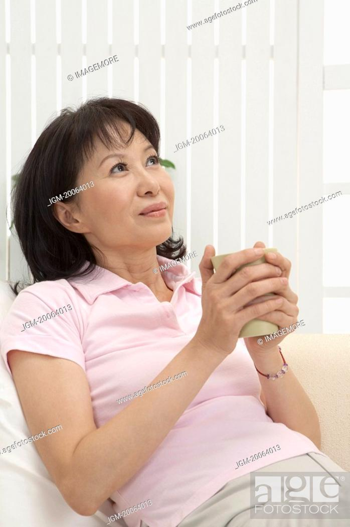 Stock Photo: Wife. Woman holding a cup and looking up with smile.