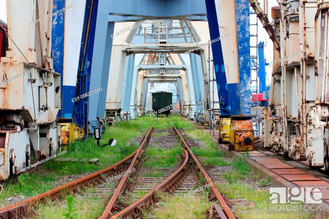 Photo de stock: Rusty overgrown train tracks run underneath decaying loading cranes at an abandoned industrial dock.