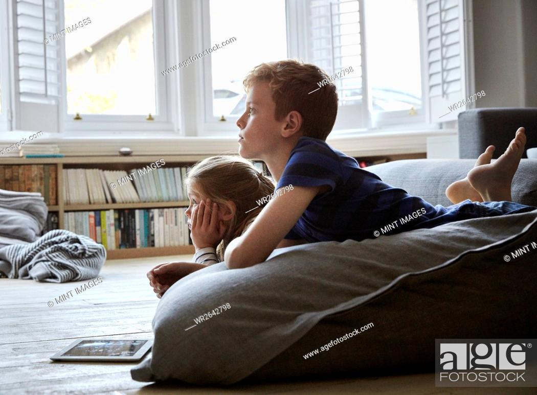 Stock Photo: A family home. Two children lying on the floor, watching television.