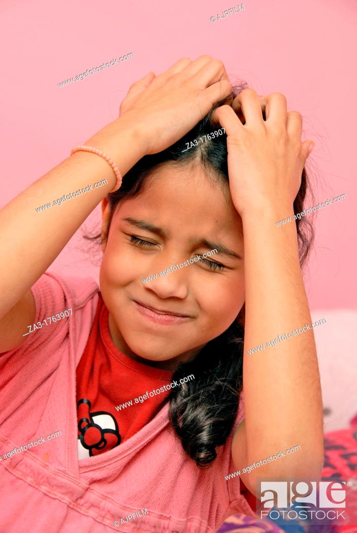 Stock Photo: Young child scratching an itch on her head.