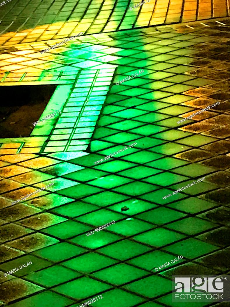 Stock Photo: Green light reflections on wet pavement.