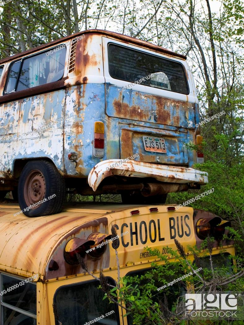 VW microbus perched atop a school bus in a salvage yard