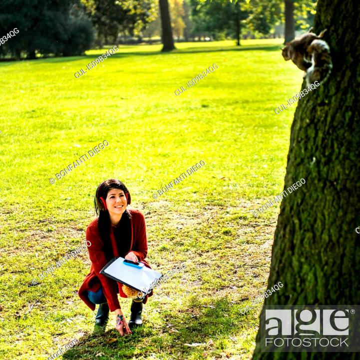 Stock Photo: Young woman crouching in park, looking at squirrel in tree.