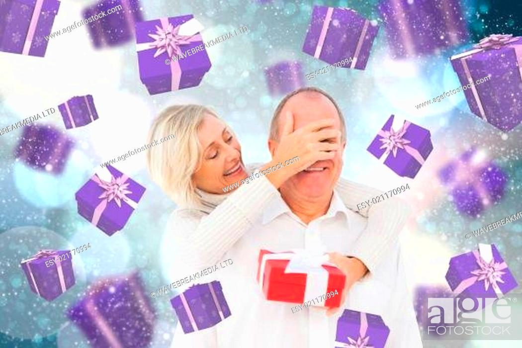 Stock Photo: Composite image of woman surprising man with gift.