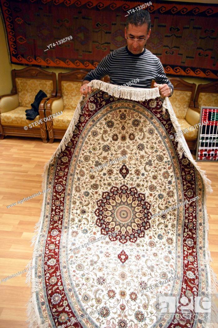 Stock Photo: Mr Mehmet Polat displaying a hand made Silk Carpet from Konya Bosphorus Carpet Weavers Coop, Istanbul, Turkey.
