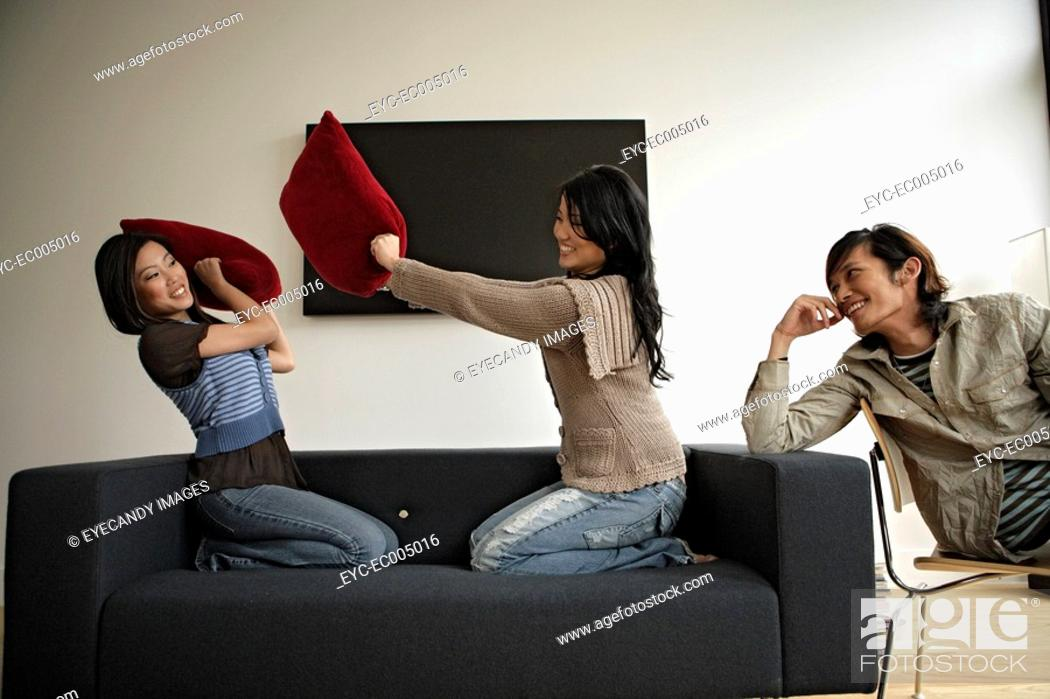 Stock Photo: Two women fighting with pillows while man observing, side view.