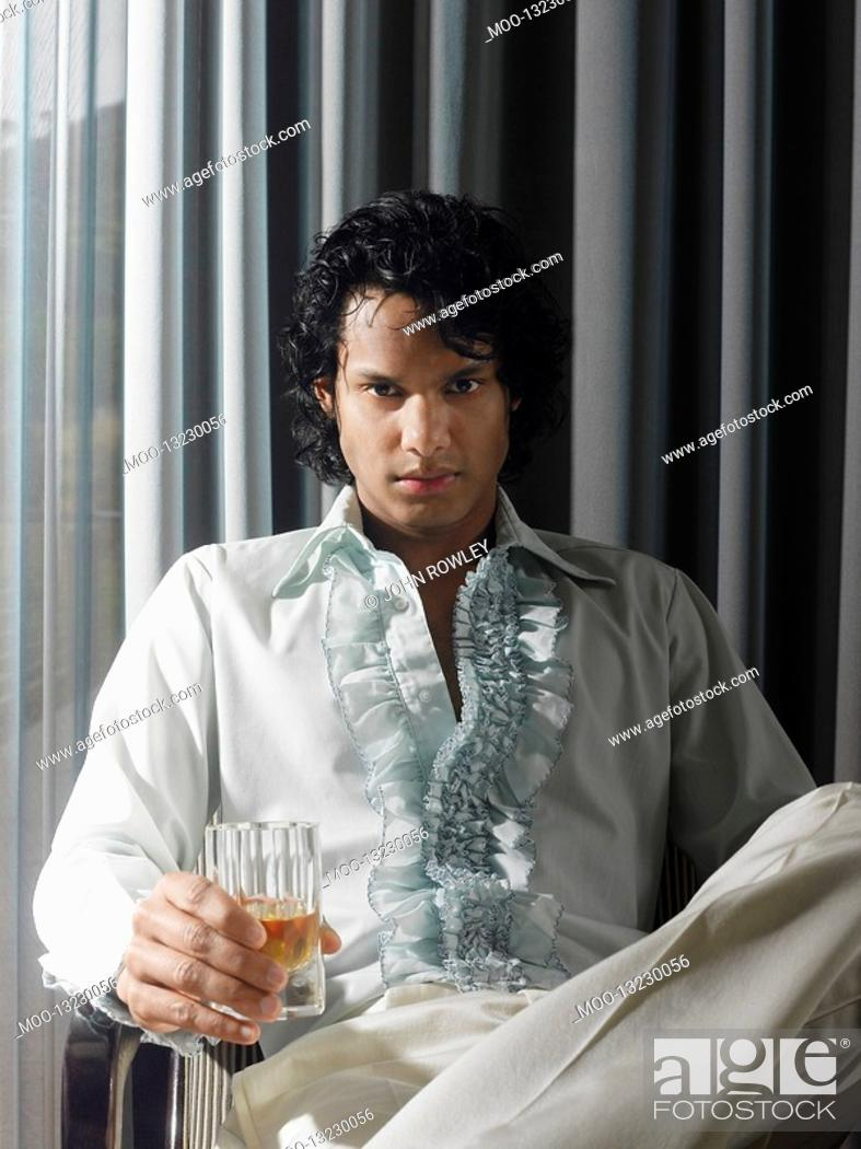 Stock Photo: Man sitting with alcoholic drink in front of curtains.