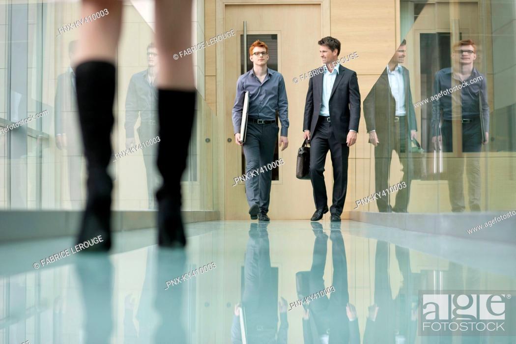 Stock Photo: Business executives walking in a corridor.