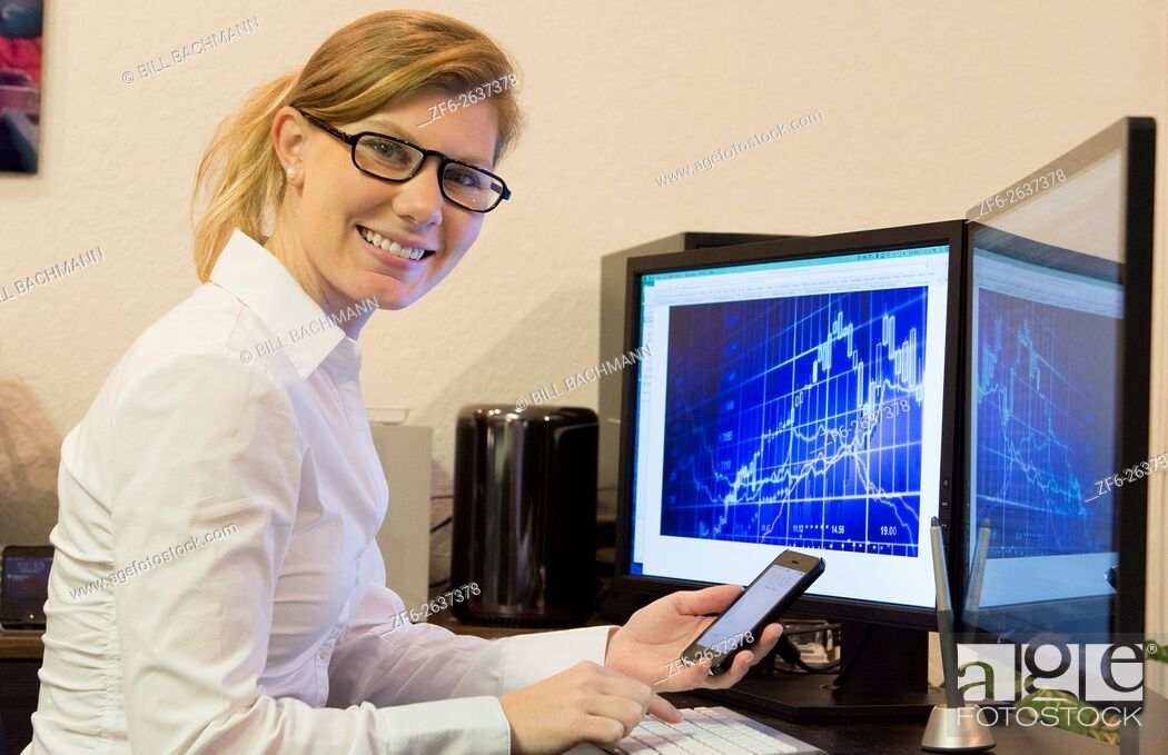 Stock Photo: Young woman working at home office using cell phone and two computer monitors doing business with clients on the internet MR Model released.