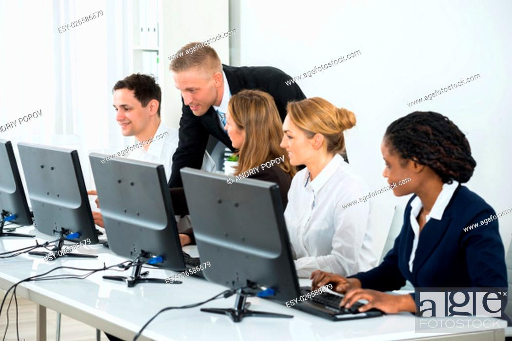 Stock Photo: Young Businessman Helping His Colleagues In The Work Of Office.