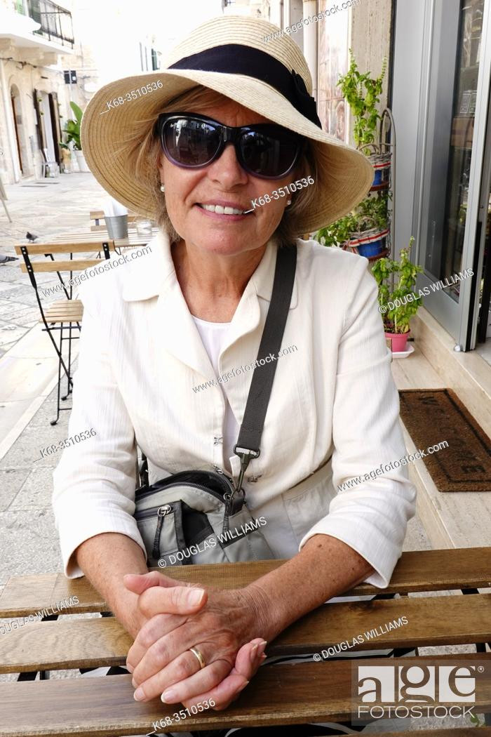 Stock Photo: Woman, 69, at a cafe in Polignano a Mare, Puglia, Italy.