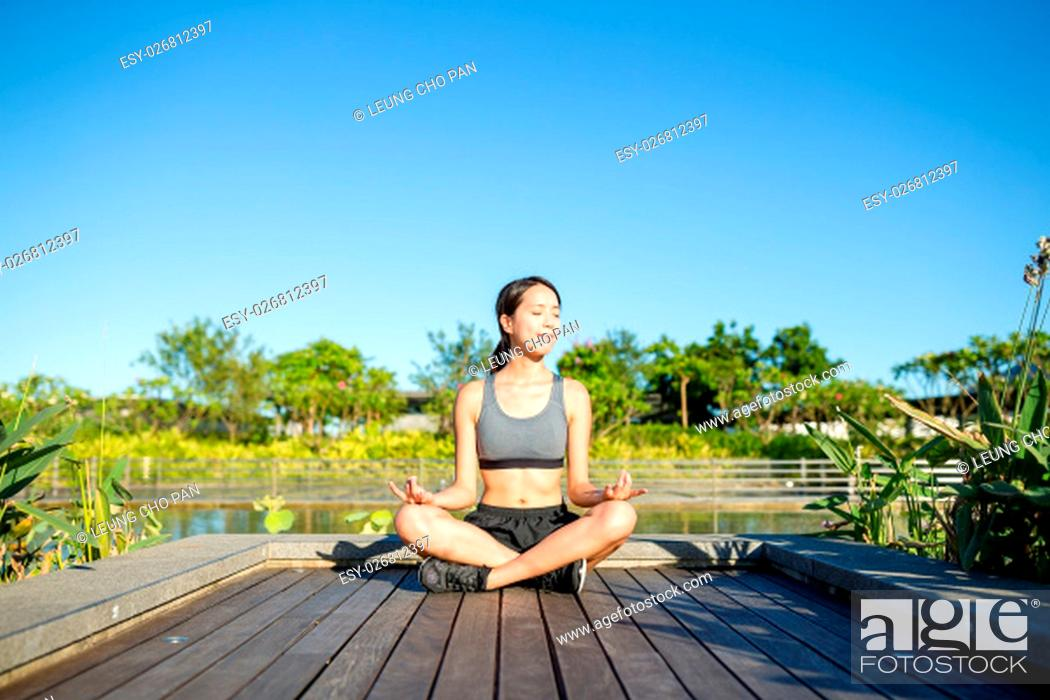Stock Photo: Young woman doing yoga exercise outdoor.