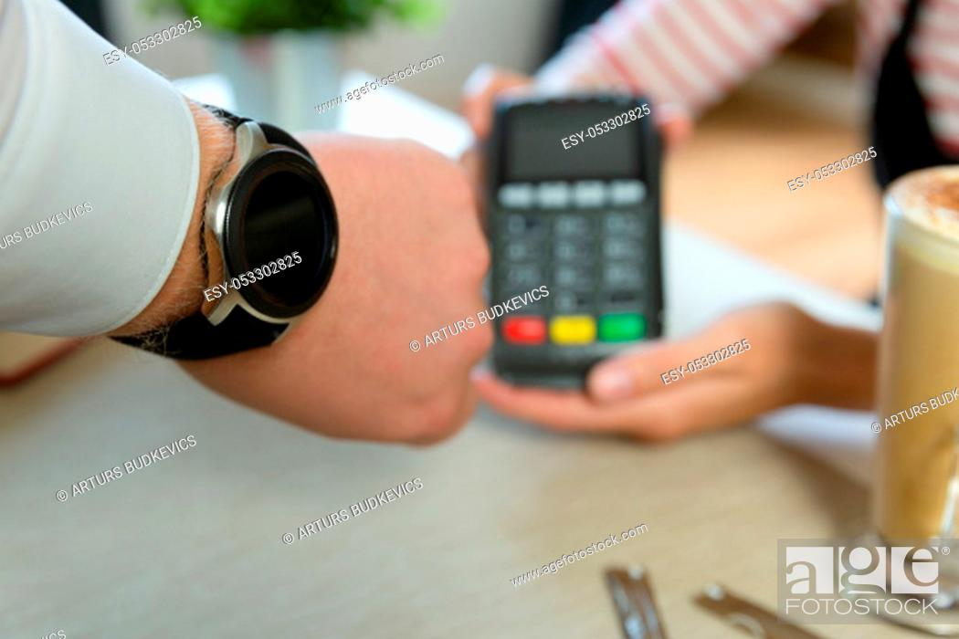 Stock Photo: Customer making wireless or contactless payment using smartwatch. Store worker accepting payment with nfc technology.