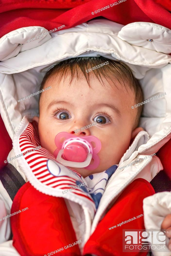 Photo de stock: Baby in the cradle sucking her pacifier. Her body covered in winter clothes.