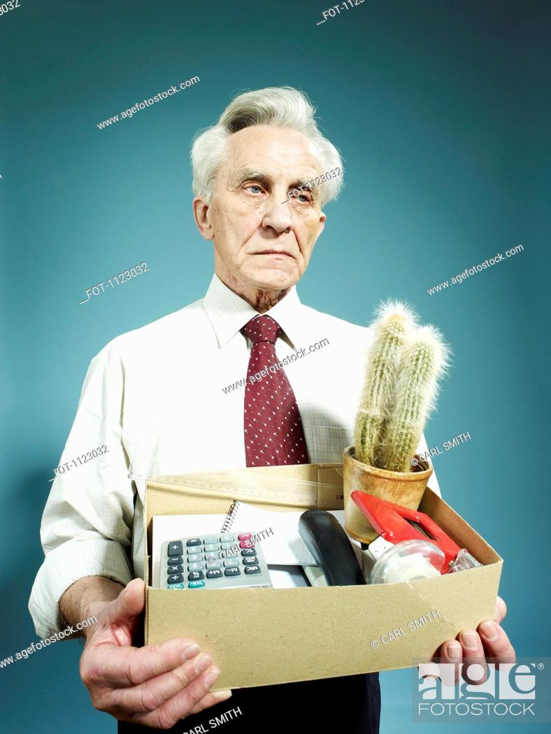 Stock Photo: A senior man carrying a box of possessions after being fired.