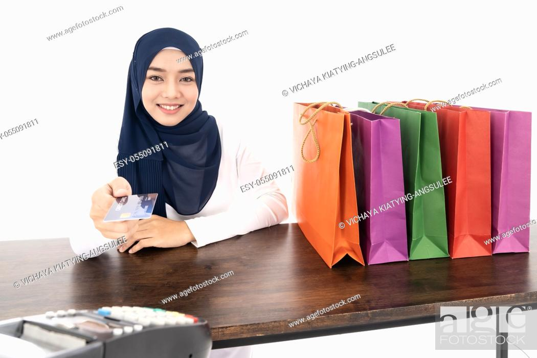 Stock Photo: Confident happy smiling female muslim woman pay for her shopping with credit card with EDC machine using as consumerism and shopaholic concept.